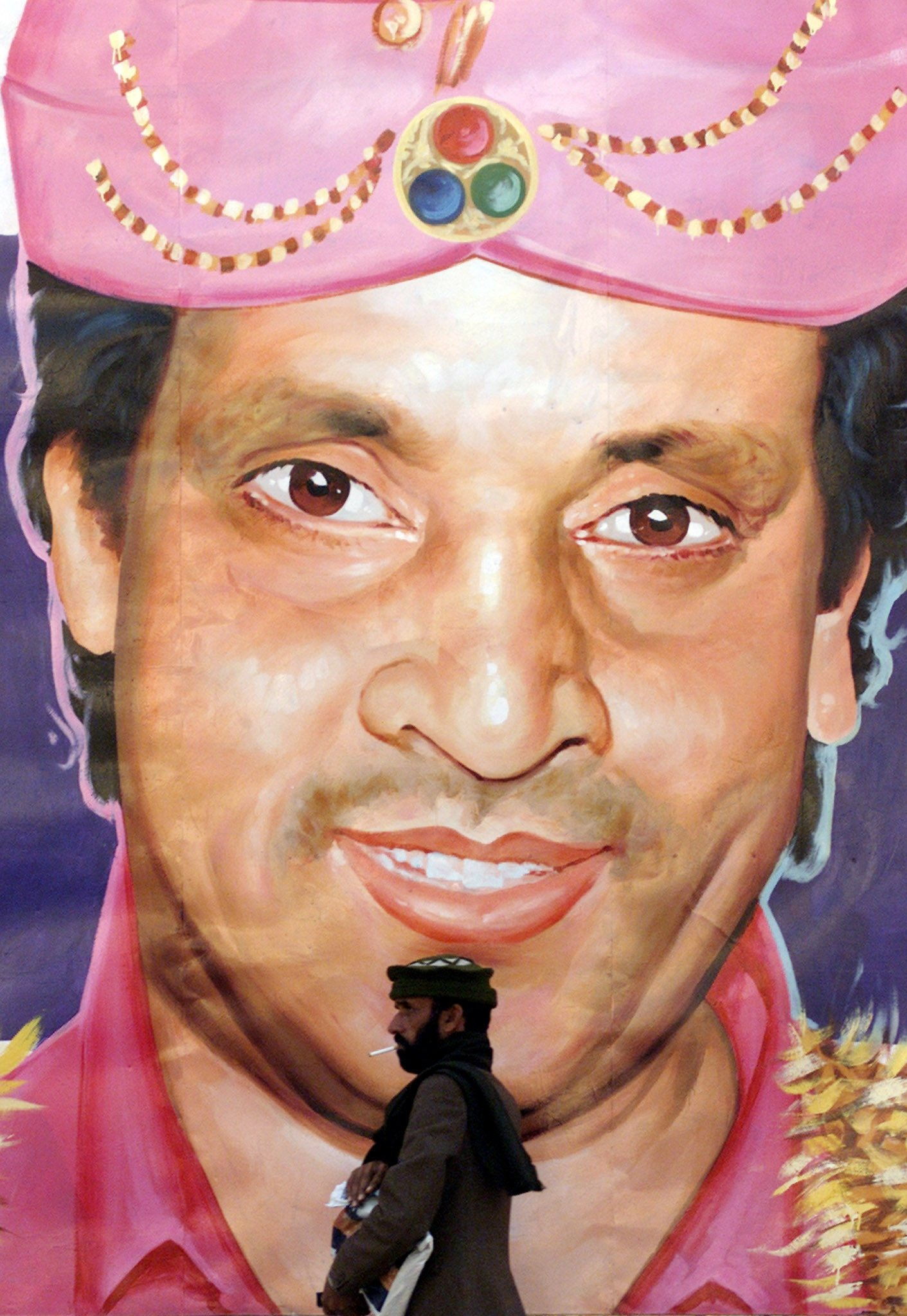 A Pakistani man walks past a huge portrait of Pakistani comedian and stage actor Umar Sharif outside a theater in Rawalpindi on the outskirts of Islamabad, Pakistan, Jan. 21, 2002. (Reuters Photo)