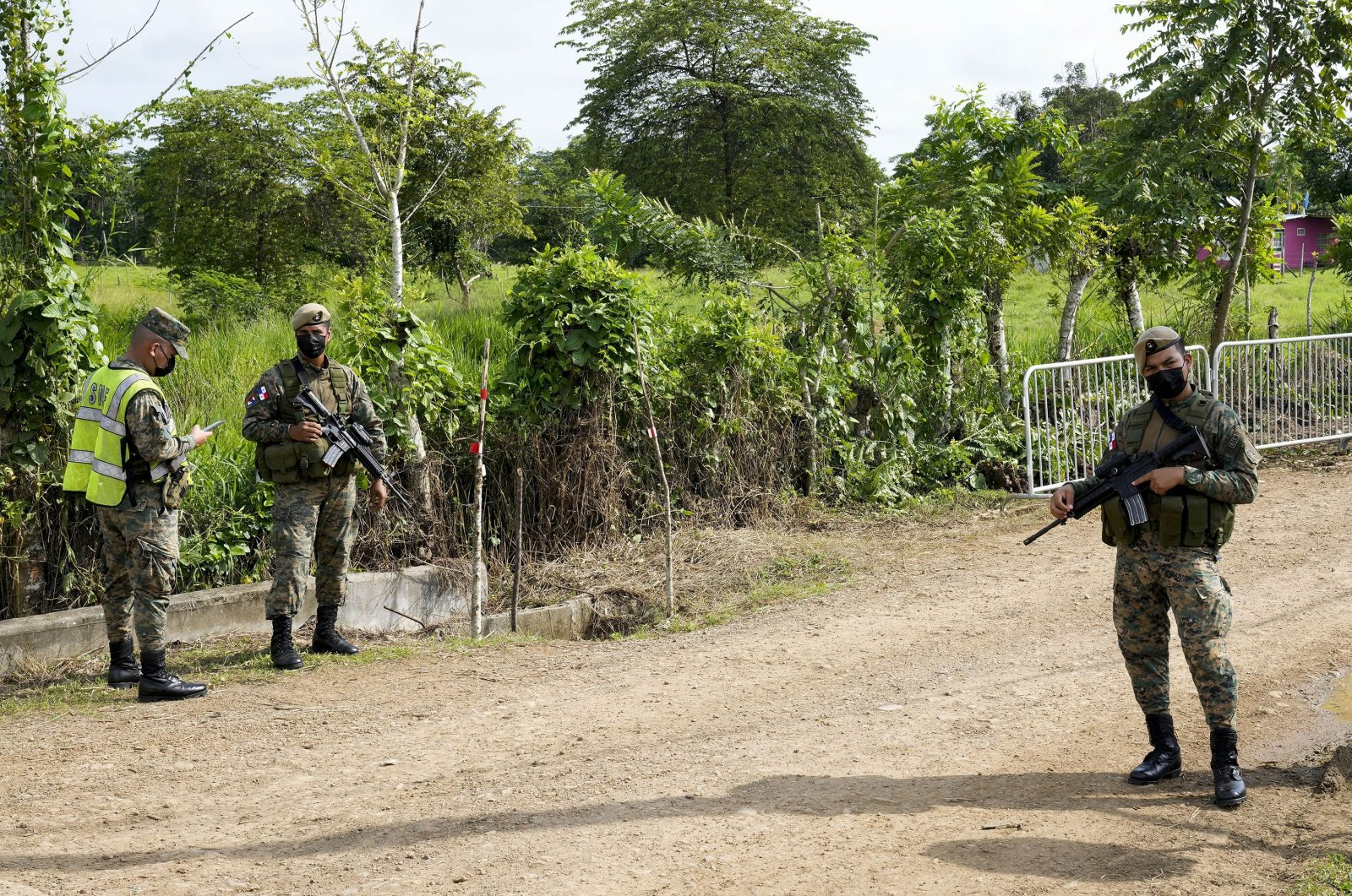 Panamanian border police stand guard outside a migrant camp before the visit of the foreign ministers from Panama and Colombia, in San Vicente, Darien province, Panama, near the border with Colombia, Aug. 6, 2021. (AP Photo)