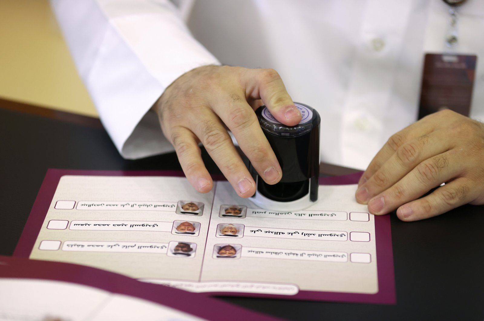 An official stamps a ballot paper in a polling station in Qatar's first legislative elections for two-thirds of the advisory Shura Council, in Doha, Qatar, Oct. 2, 2021. (Reuters Photo)