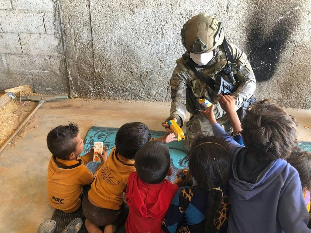 A Turkish soldier distributes aid to children in the Operation Peace Spring zone, northern Syria, Sept. 22, 2021. (AA Photo)