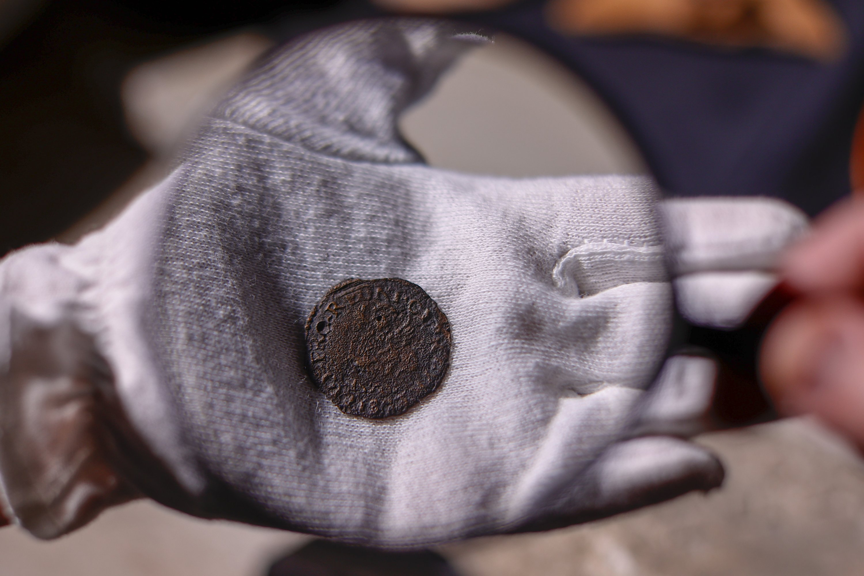 A coin found in the ancient city of Phanagoria seen through a magnifying glass, Russia, Oct. 1, 2021. (AA Photo)