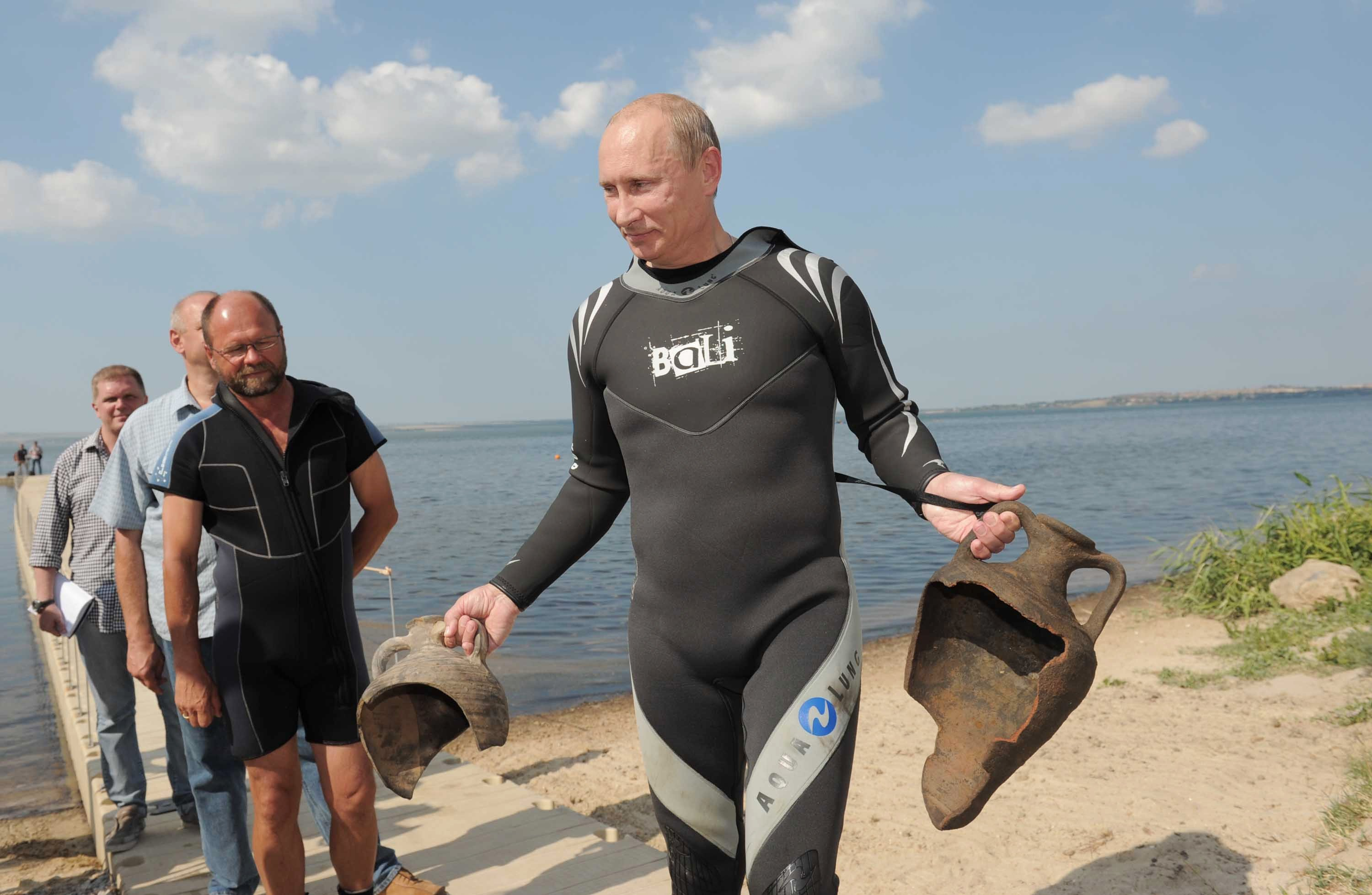Russian Prime Minister Vladimir Putin carries artifacts he recovered while diving at the archaeological site of Phanagoria off the Taman peninsular in southern Russia, Aug. 10, 2011. (Reuters Photo)