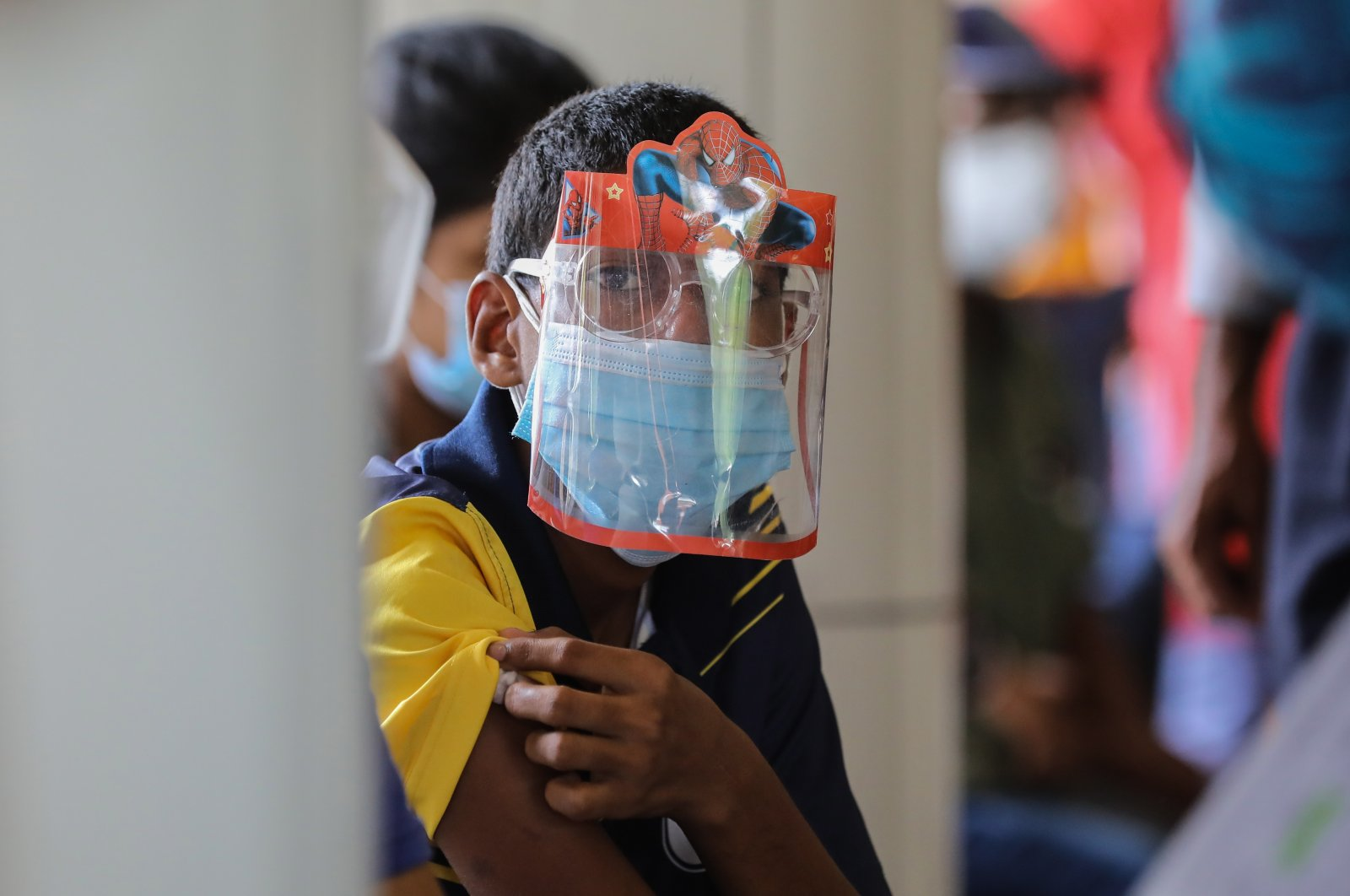 A Sri Lankan boy with a face shield with his hero receives his COVID-19 vaccine at a Hospital during an island-wide lockdown as a preventive measure against the spread of COVID-19, Colombo, Sri Lanka, Sept. 30, 2021. (EPA Photo)
