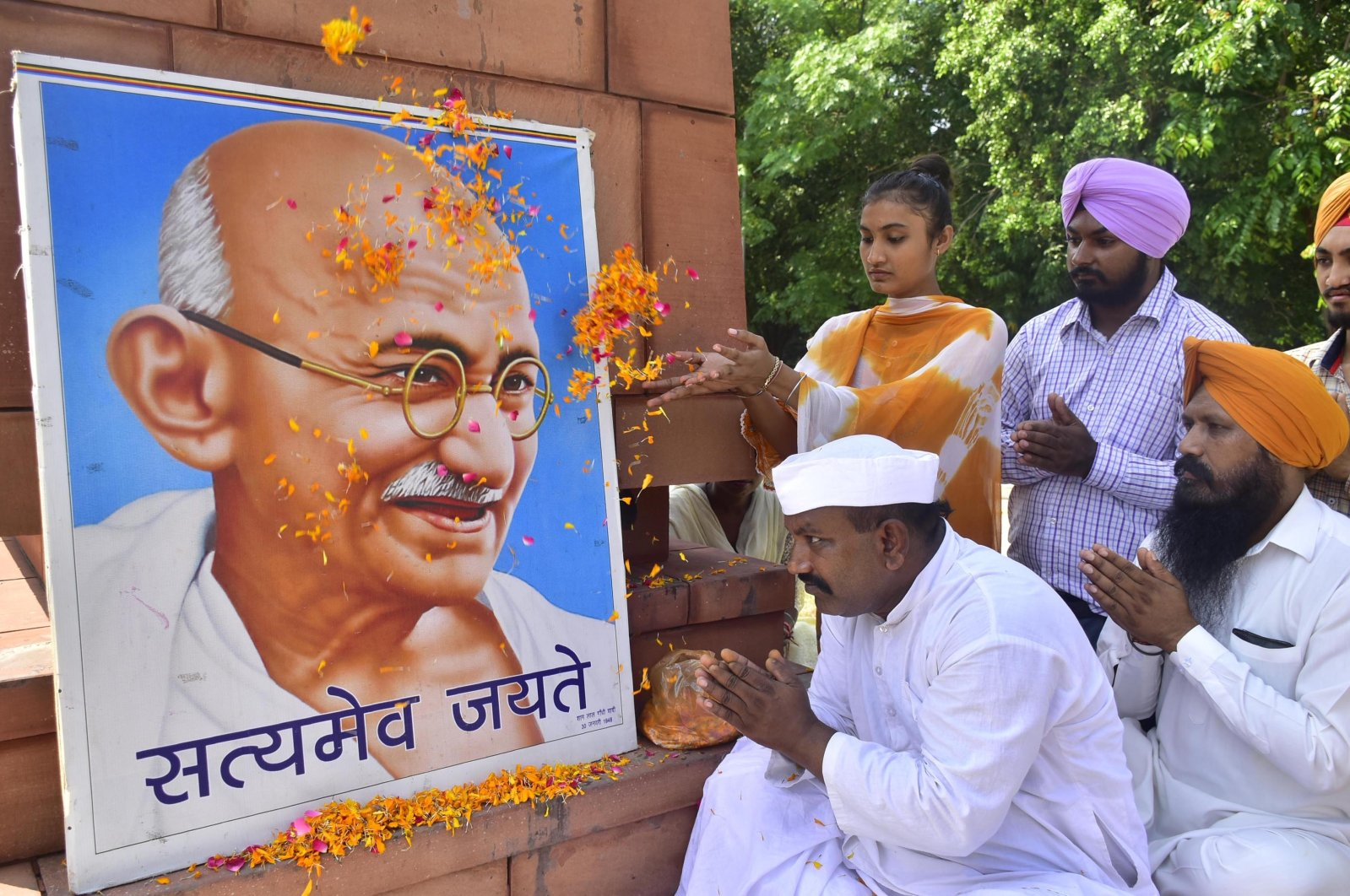 Social worker Shyam Lal Gandhi (L) and others pay floral tribute to Mahatma Gandhi on the occasion of the anniversary of his birth, Amritsar, India, Oct. 2, 2021.  (Photo by Sameer Sehgal/Hindustan Times via Getty Images)