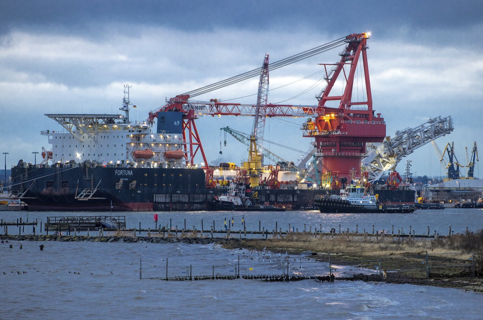 """In this Jan. 14, 2021 file photo, tugboats get into position on the Russian pipe-laying vessel """"Fortuna"""" in the port of Wismar, Germany. (AP Photo)"""