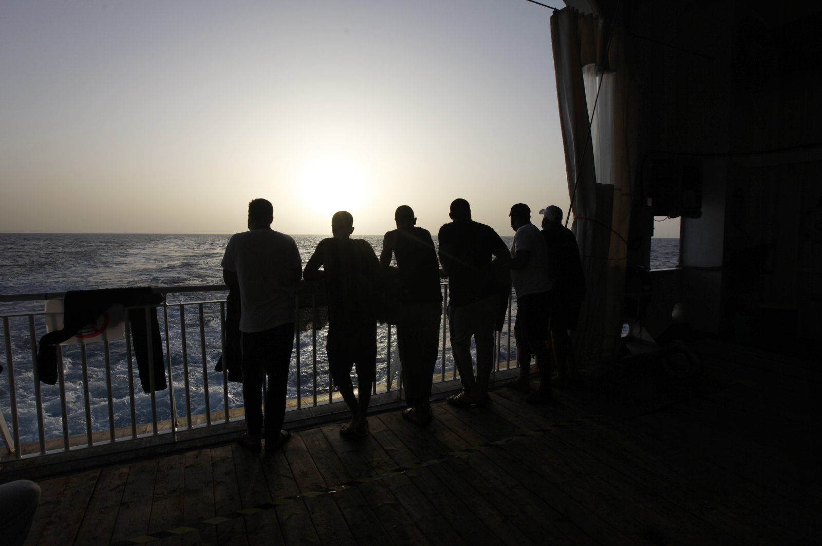 Arab migrants, including three Libyans, two Tunisians and a Moroccan, gaze at the Mediterranean Sea, on the deck of the Geo Barents, a rescue vessel operated by MSF (Doctors Without Borders) off Libya, in the Central Mediterranean route, Sept. 22, 2021. (AP Photo)