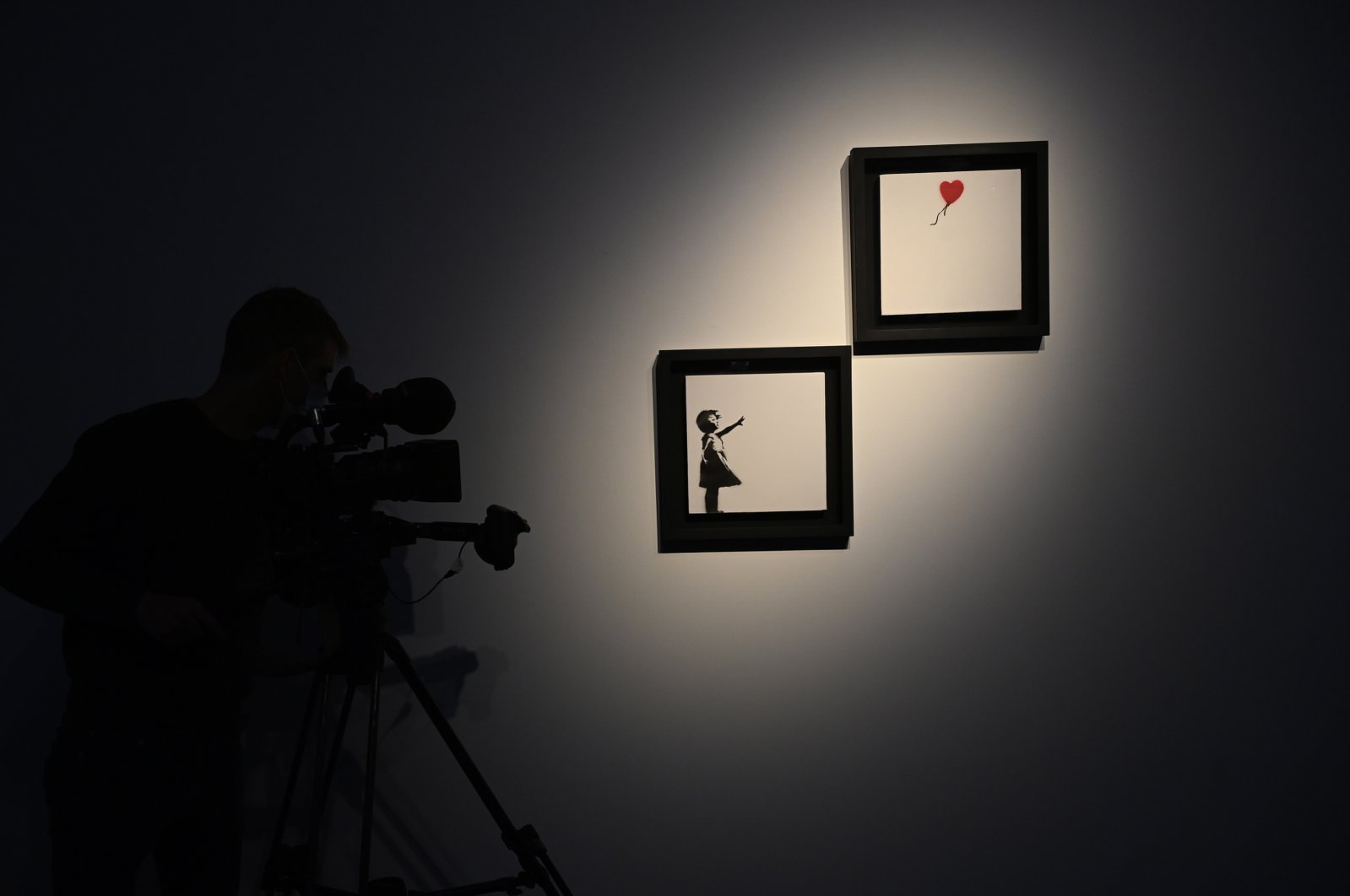 """A cameraman stands next to artwork by British artist Banksy titled """"Girl and Ballon"""" (two parts) during a press view at the Christie's auction house in London, Britain, Oct. 1, 2021. (EPA Photo)"""