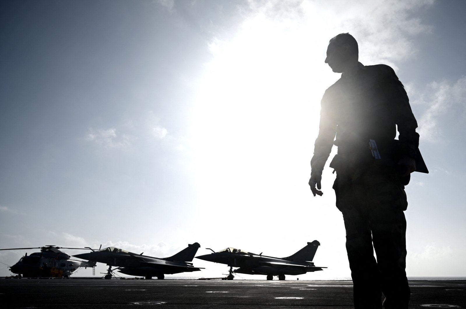 """A military officer looks on in front of Rafale jet fighters on the deck of the French aircraft carrier """"Charles de Gaulle"""" at sea, off the coast of Hyeres, Jan. 23, 2020 (AFP File Photo)"""