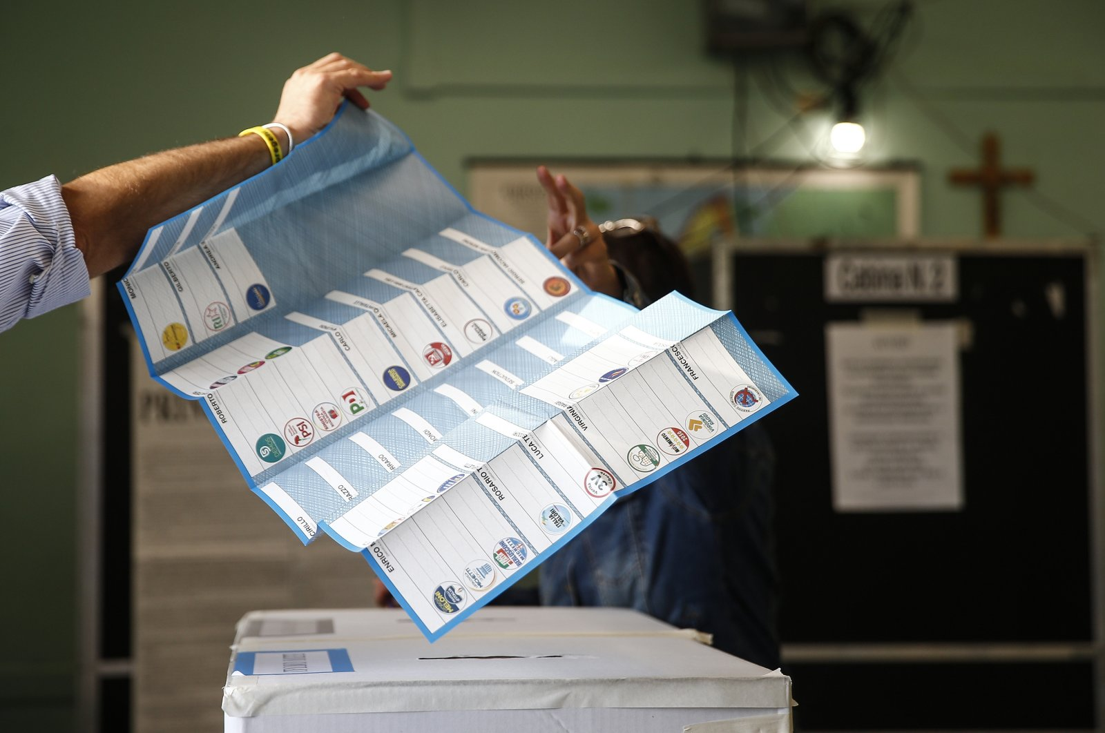 A man receives his ballots at a polling station, in Rome, Italy, Oct. 3, 2021. (AP Photo)