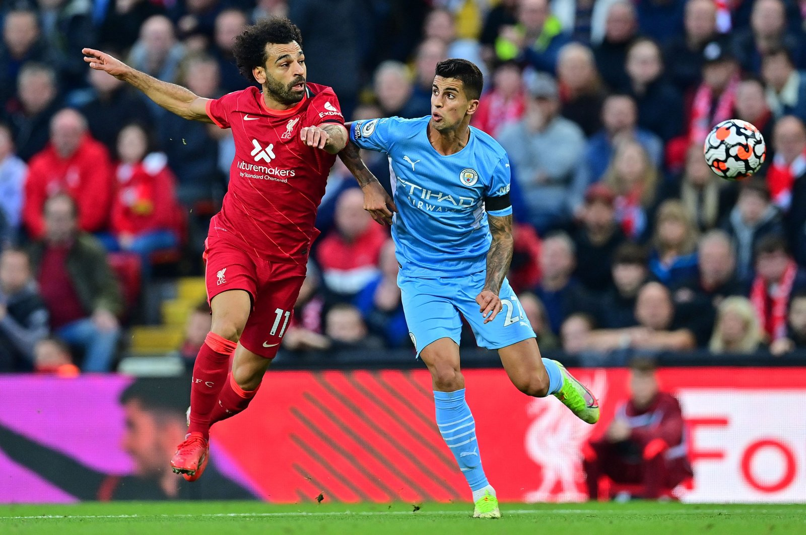 Liverpool's Egyptian midfielder Mohamed Salah (L) challenges Manchester City's Spanish midfielder Rodrigo during the English Premier League football match between Liverpool and Manchester City at Anfield in Liverpool, northwest England, on Oct. 3, 2021. (AFP Photo)