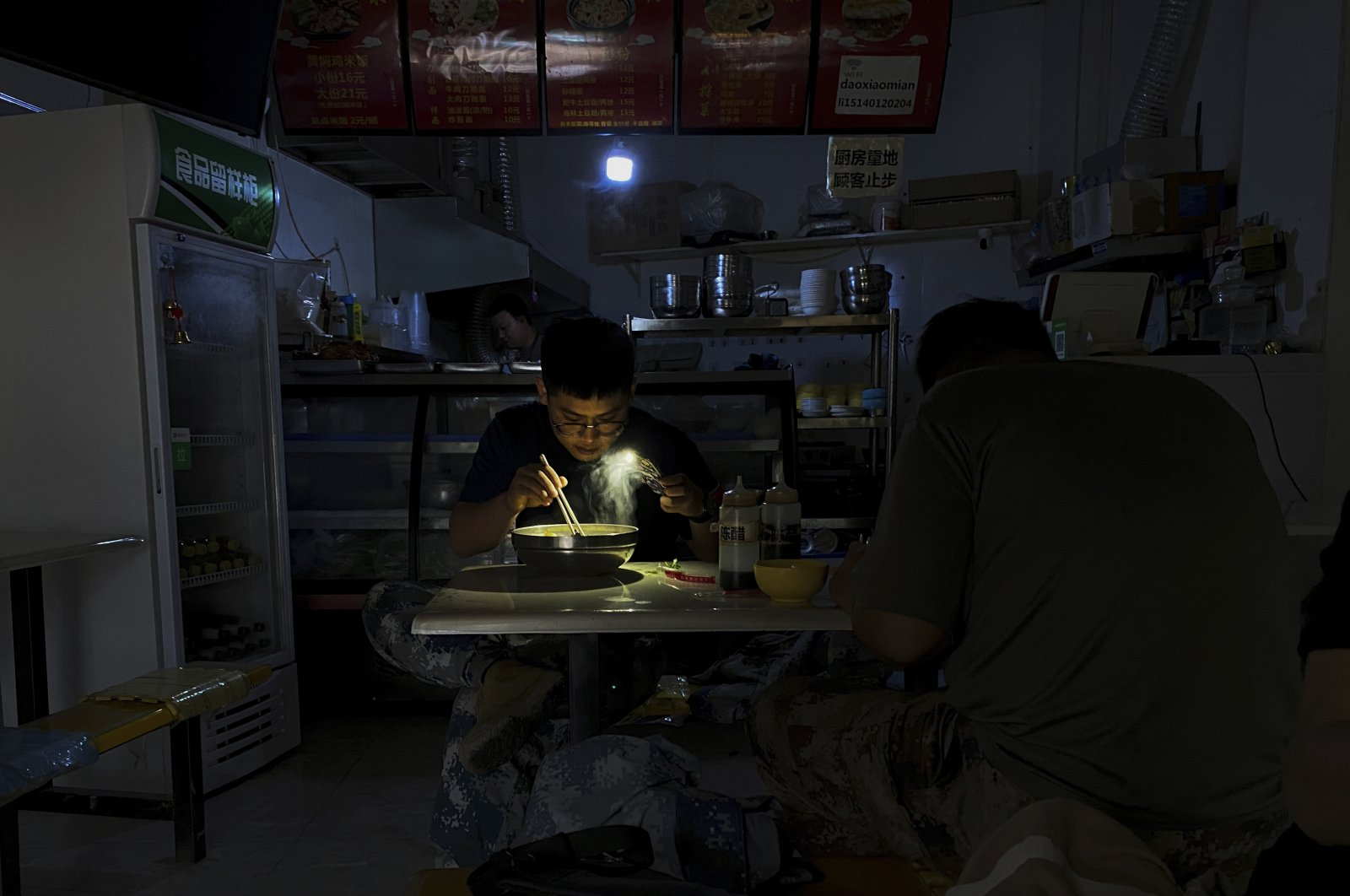 A man uses his smartphone flashlight to light up his bowl of noodles as he eats his breakfast at a restaurant during a blackout in Shenyang in the northeastern Liaoning Province, China, Sept. 29, 2021. (AP Photo)