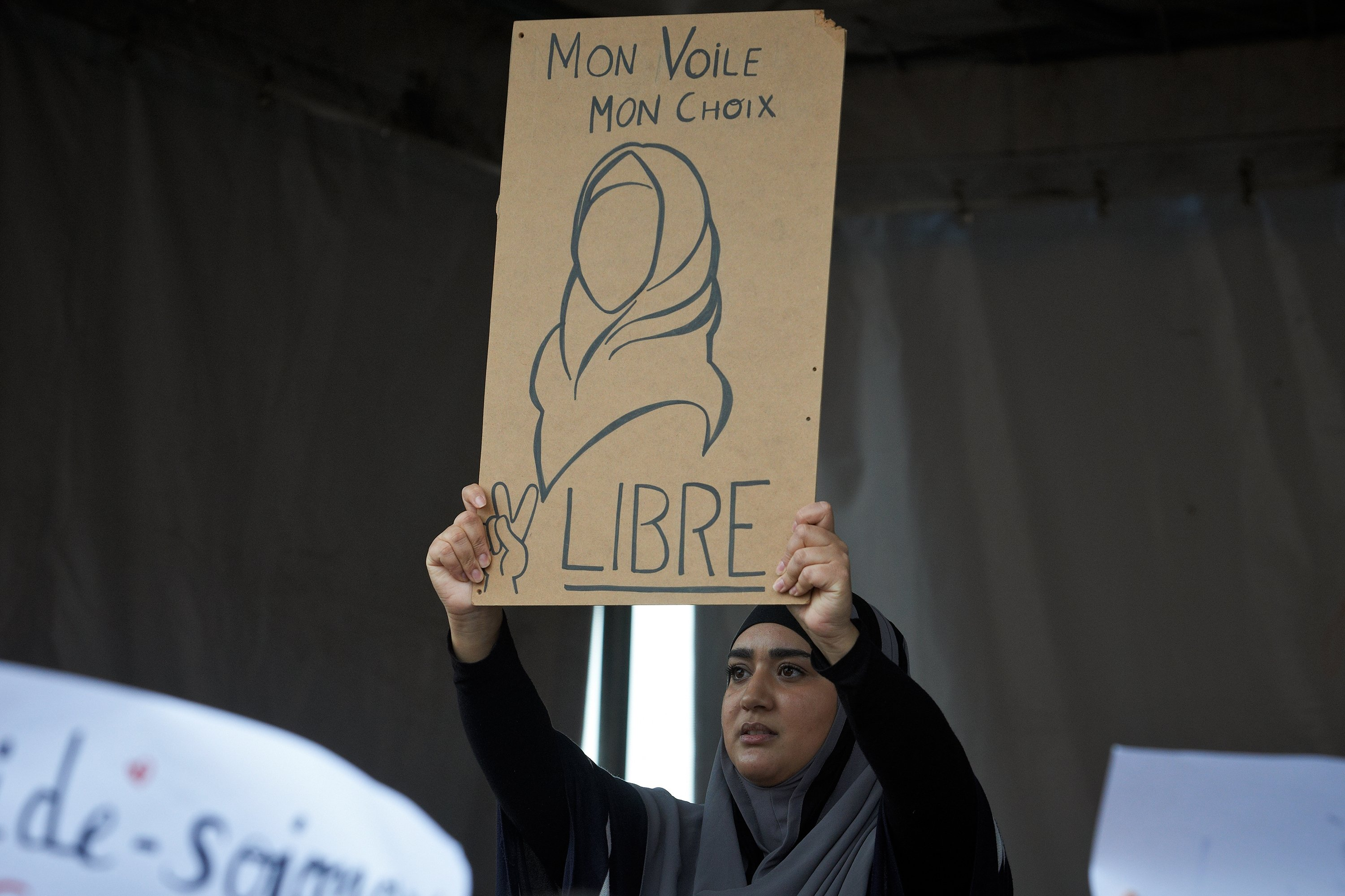 A woman with a headscarf shows a drawing reading 'My veil, my choice, Free.' People gathered against Islamophobia on the main square of Toulouse, France, Oct. 27, 2019. (Getty Images Photo)