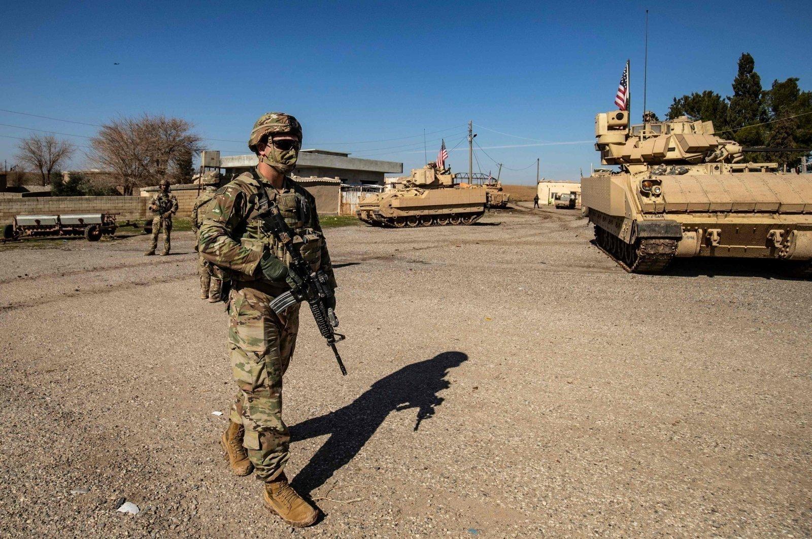 A U.S. soldier walks near a Bradley Fighting Vehicle (BFV) during a patrol in the countryside near al-Malikiyah (Derik) in Hassakeh province, northeastern Syria, Feb. 2, 2021. (AFP Photo)