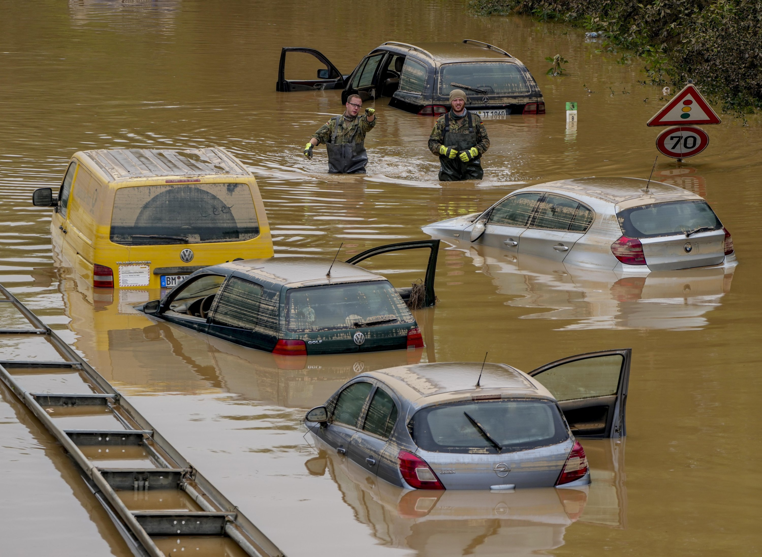 People check for victims in flooded cars on a road in Erftstadt, Germany, following heavy rainfall that broke the banks of the Erft river, causing massive damage, July 17, 2021. (AP Photo)