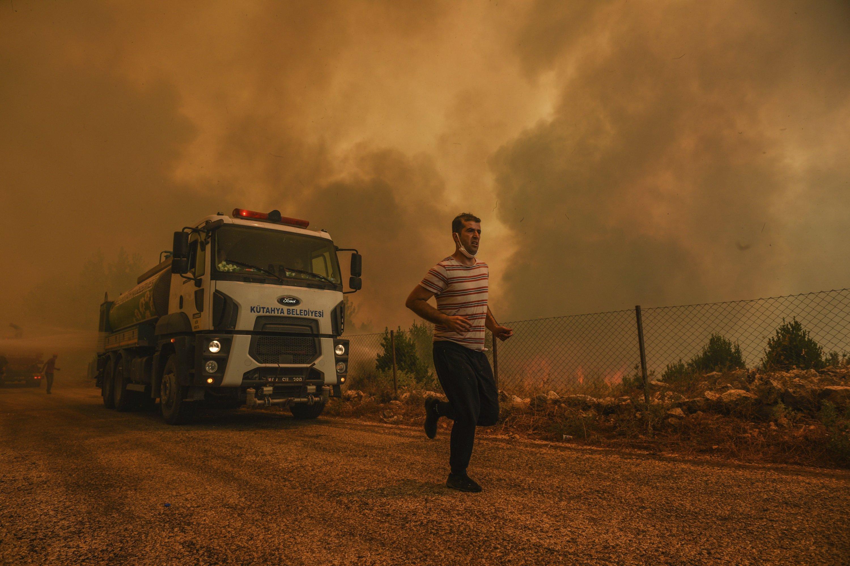 A man runs as a forest fire devastates Sirtkoy village, near Manavgat, Antalya, Turkey, Aug. 1, 2021. (AP Photo)