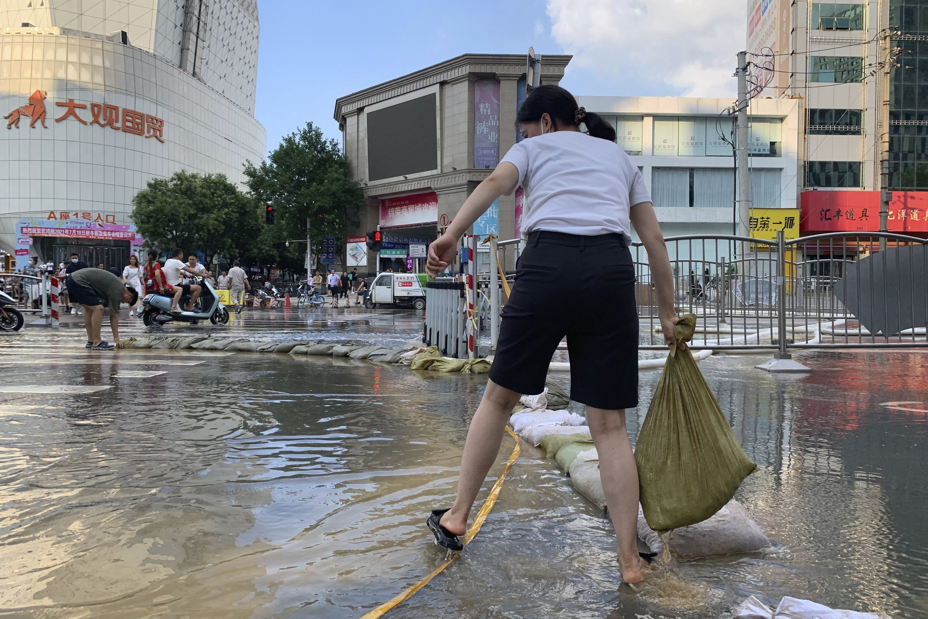 A woman moves a sandbag along a flooded road in the aftermath of the heaviest recorded rainfall in Zhengzhou, Henan province, central China, July 24, 2021. (AP Photo)
