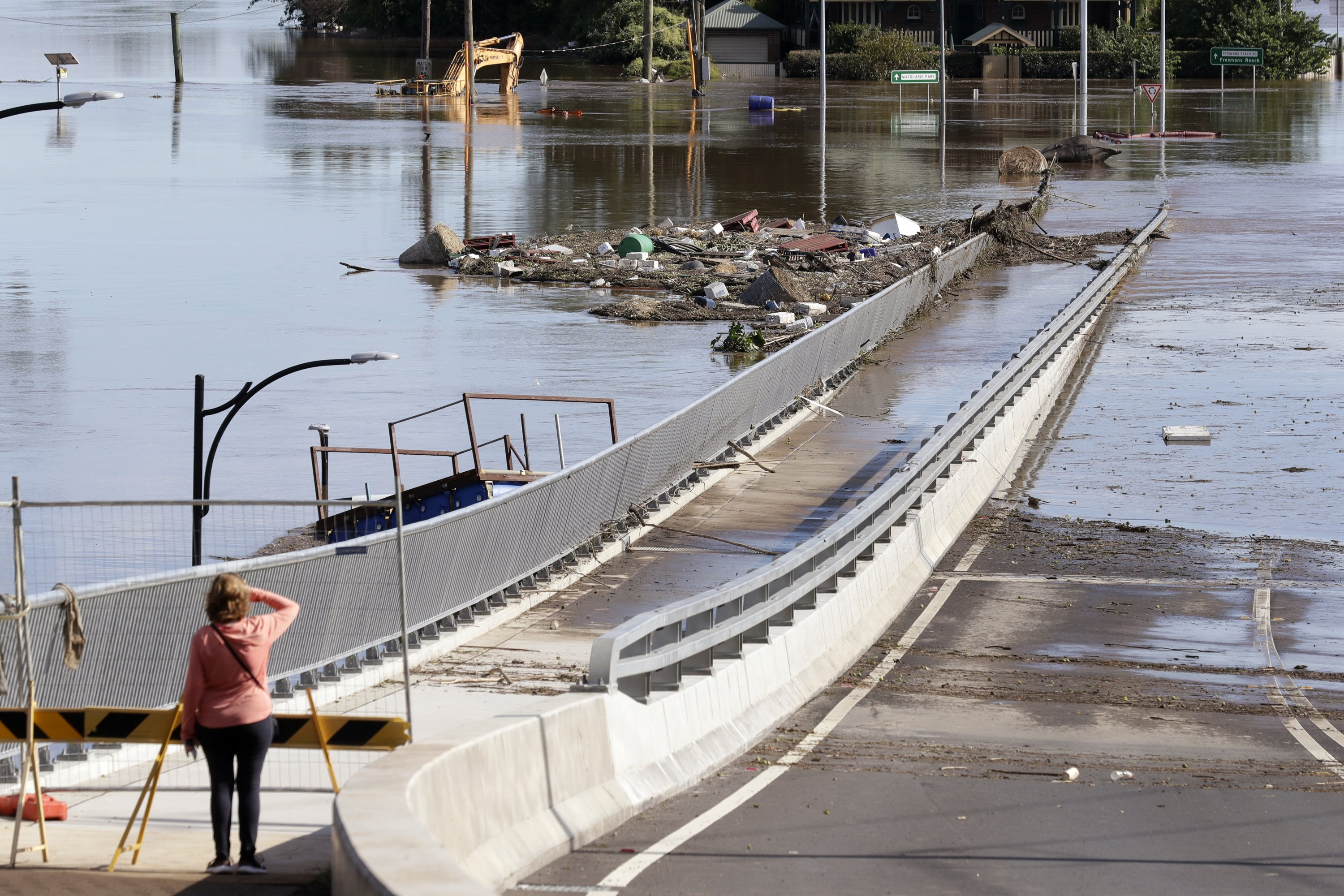 A woman looks at debris caught on a submerged bridge in Windsor, northwest of Sydney, Australia, March 25, 2021. (AP Photo)