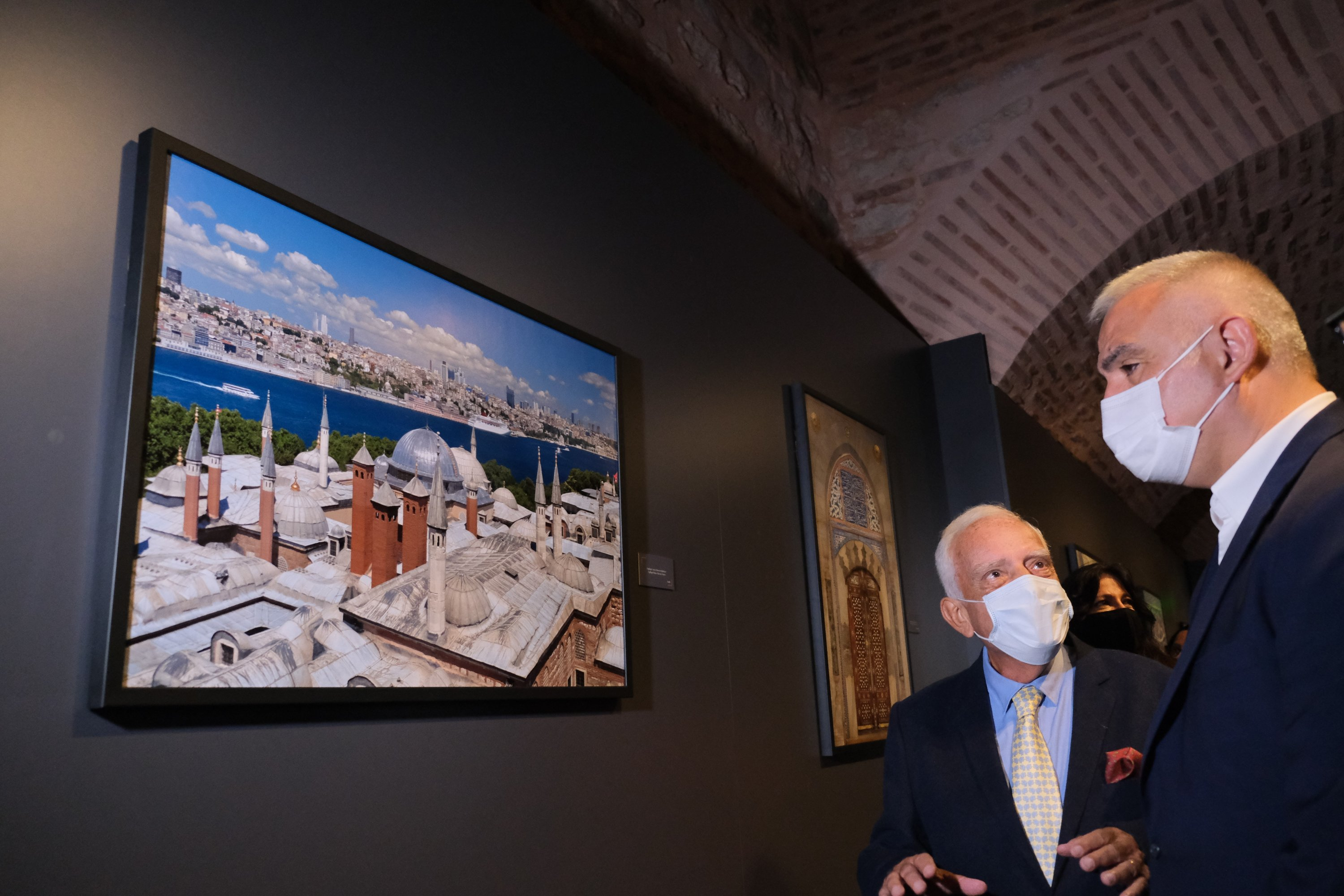 """Izzet Keribar (L) and Minister of Culture and Tourism Mehmet Nuri Ersoy examine a photo of Hagia Sophia Grand Mosque by Izzet Keribar in the exhibition """"Heritage: Ottoman Architecture and Tile Art in Istanbul,"""" Museum of Turkish and Islamic Arts, Istanbul, Turkey, Oct. 2, 2021. (AA Photo)"""