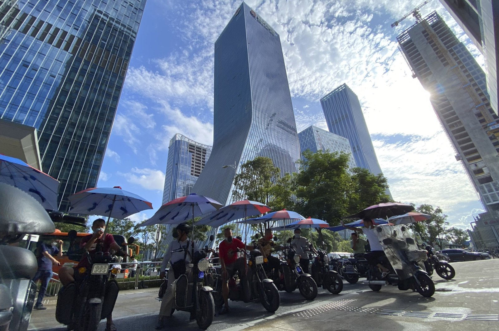Men on electric bikes wait for riders near the Evergrande headquarters (C) in Shenzhen, China, Sept. 24, 2021. (AP Photo)