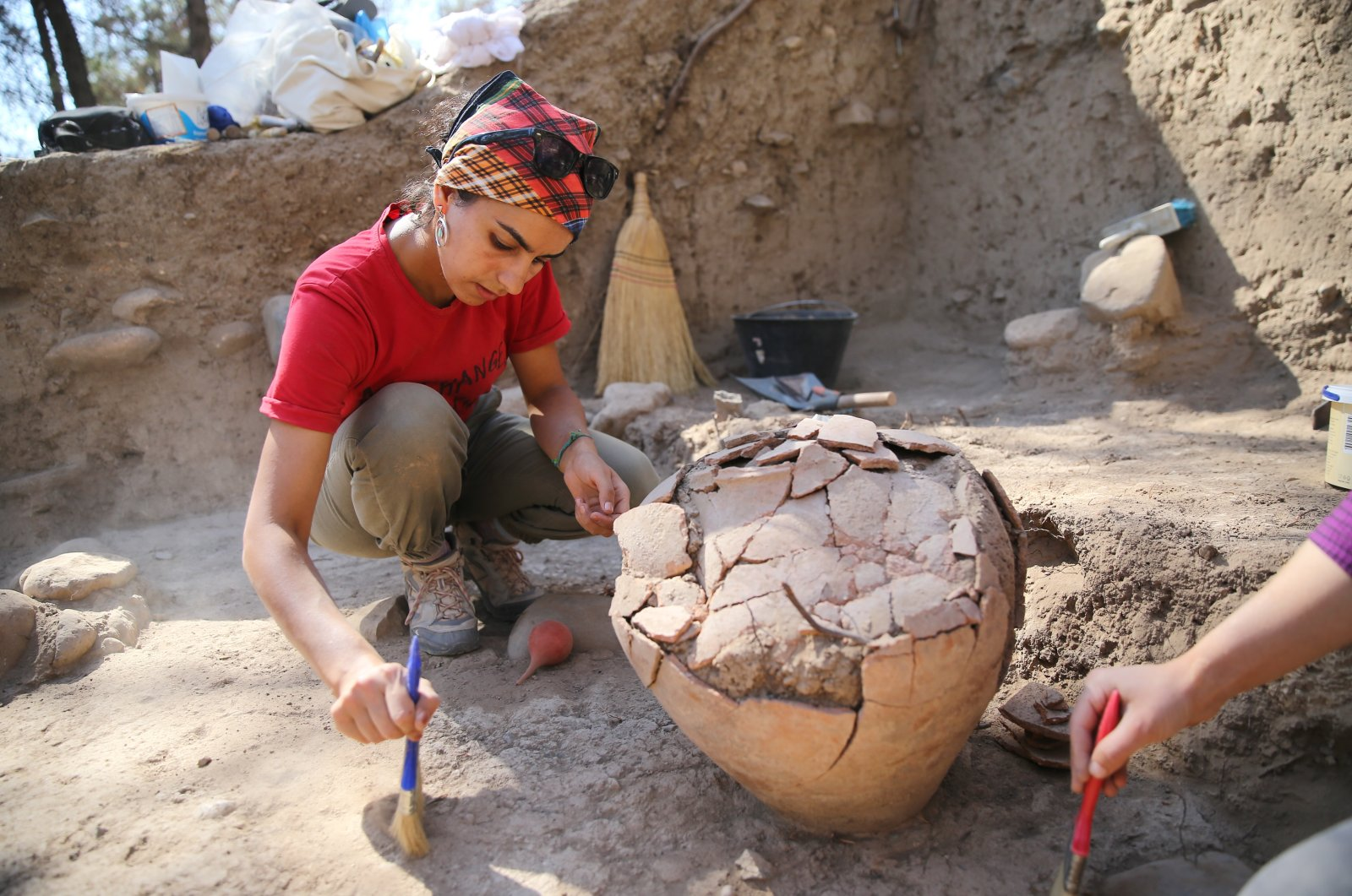 Archaeologists work on the 4,500-year-old jar in the Yumuktepe Mound, Mersin, southern Turkey, Oct. 3, 2021. (AA Photo)