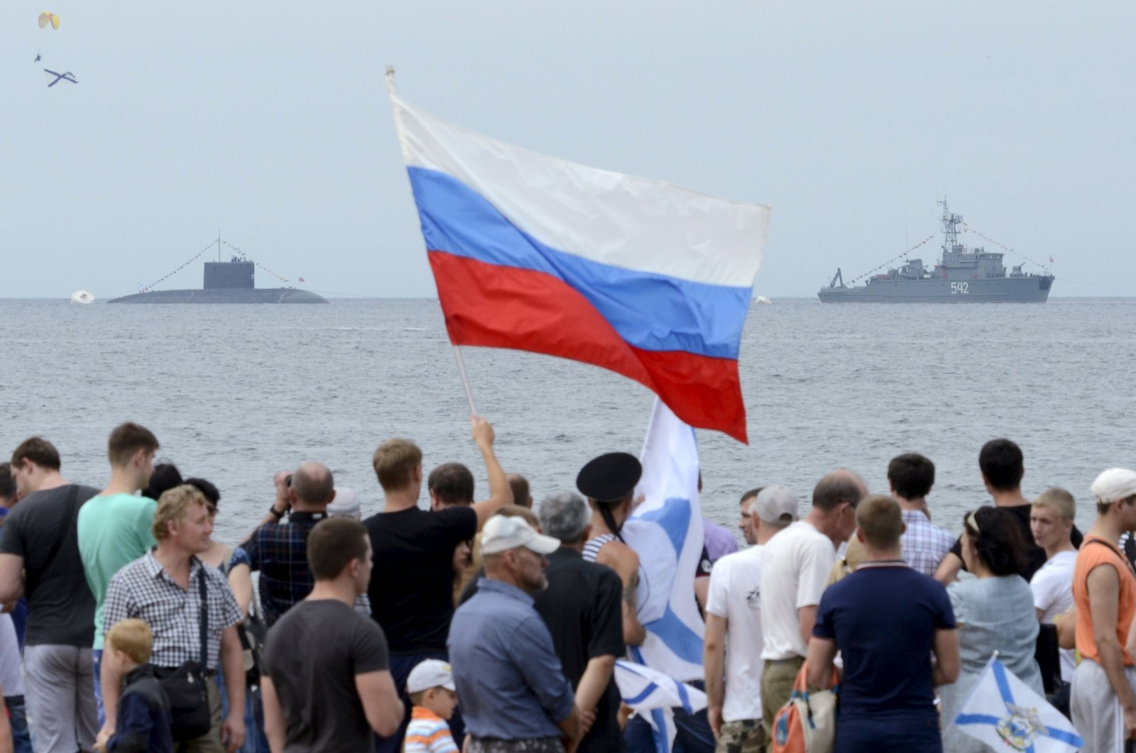 People gather to watch celebrations for Navy Day, with a Russian warship and a submarine seen in the background, in the far eastern city of Vladivostok, Russia, July 26, 2015. (Reuters Photo)
