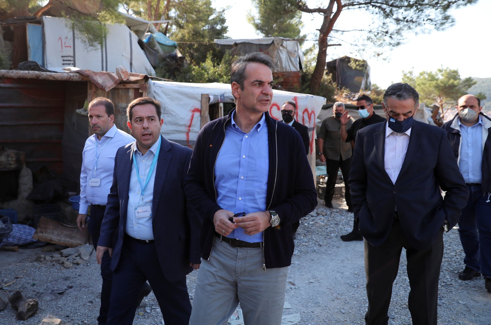 Greek Prime Minister Kyriakos Mitsotakis (C) and Migration Minister Notis Mitarachi (L) visit a disused migrant camp on the island of Samos, Greece, Oct. 1, 2021. (Reuters Photo)