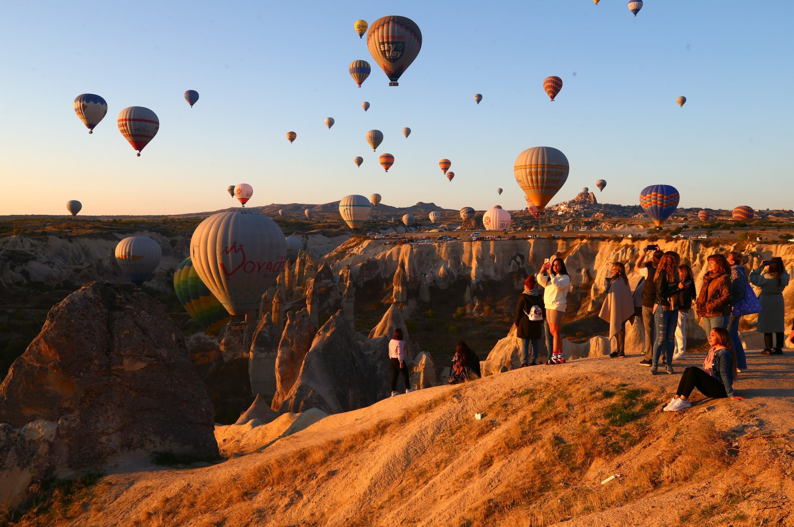 Tourists watch and take photographs as air balloons take to the sky, inNevşehir, Turkey, Oct. 3, 2021. (AA Photo)