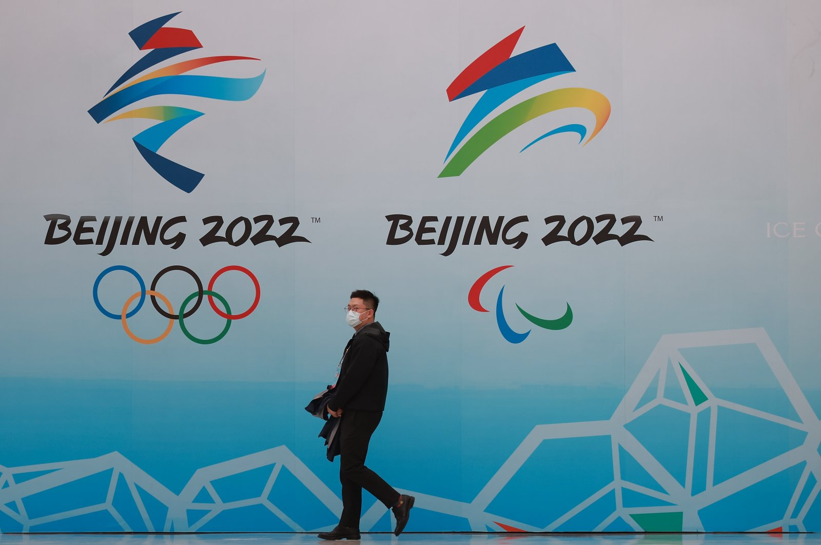 A Chinese man wears a protective mask as he walks in front of the logos of the 2022 Beijing Winter Olympics, in Beijing, China, April 9, 2021. (Getty Images)