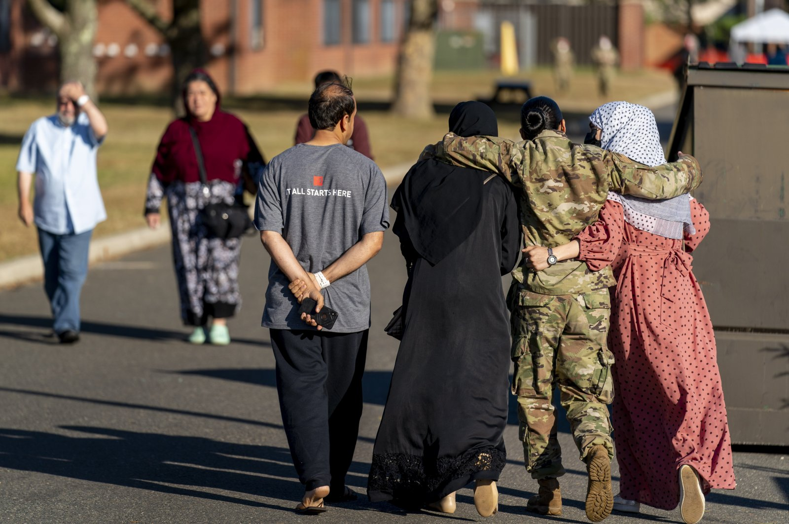 A female member of the U.S. military puts her arms around two female Afghan refugees after they spoke with Secretary of Defense Lloyd Austin as he visits an Afghan refugee camp on Joint Base McGuire Dix Lakehurst, New Jersey, U.S., Sept. 27, 2021. (AP Photo)