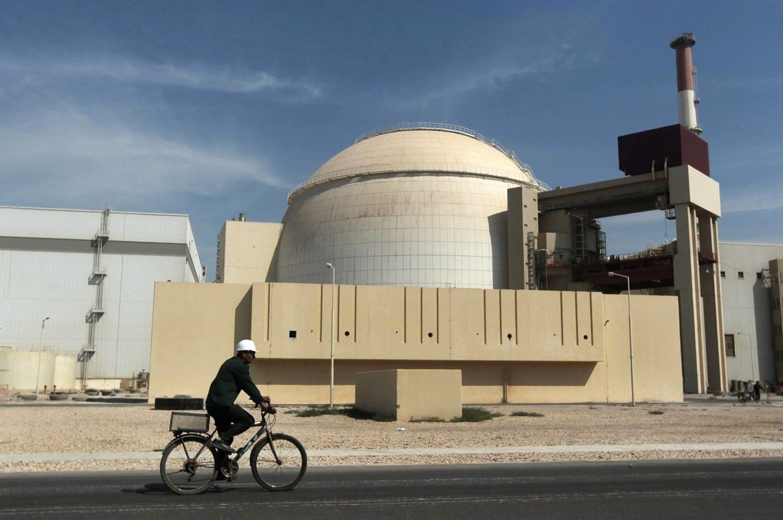 A worker rides a bicycle in front of the reactor building of the Bushehr nuclear power plant, just outside the southern city of Bushehr, Iran, Oct. 26, 2010. (AP Photo)