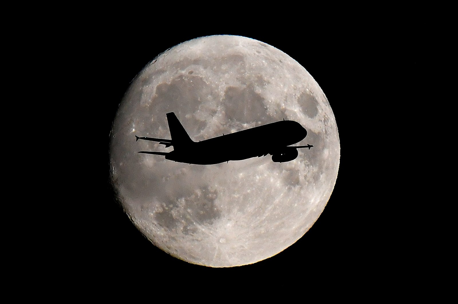 A passenger plane passes in front of the moon as it makes its final landing approach to Heathrow Airport in London, Britain, Sept. 12, 2019. (Reuters Photo)