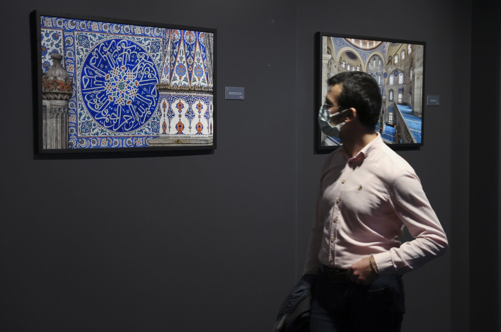 """A visitor examines a photo by Izzet Keribar in the exhibition """"Heritage: Ottoman Architecture and Tile Art in Istanbul,"""" Museum of Turkish and Islamic Arts, Istanbul, Turkey, Oct. 2, 2021. (AA Photo)"""