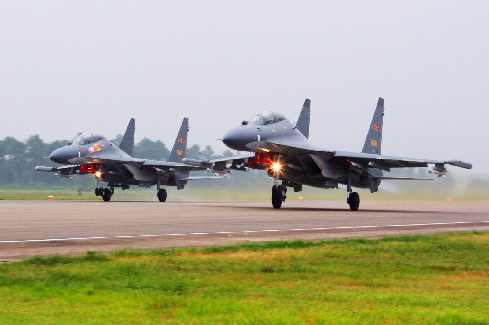 In this undated file photo released by China's Xinhua News Agency, two Chinese SU-30 fighter jets take off from an unspecified location to fly a patrol over the South China Sea. (AP Photo)