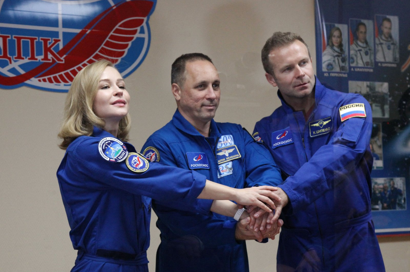Crew members, cosmonaut Anton Shkaplerov (C), actress Yulia Peresild (L) and director Klim Shipenko, shake hands during a news conference ahead of the expedition to the International Space Station (ISS) at the Baikonur Cosmodrome, Kazakhstan, Oct. 4, 2021. (Roscosmos via AFP)