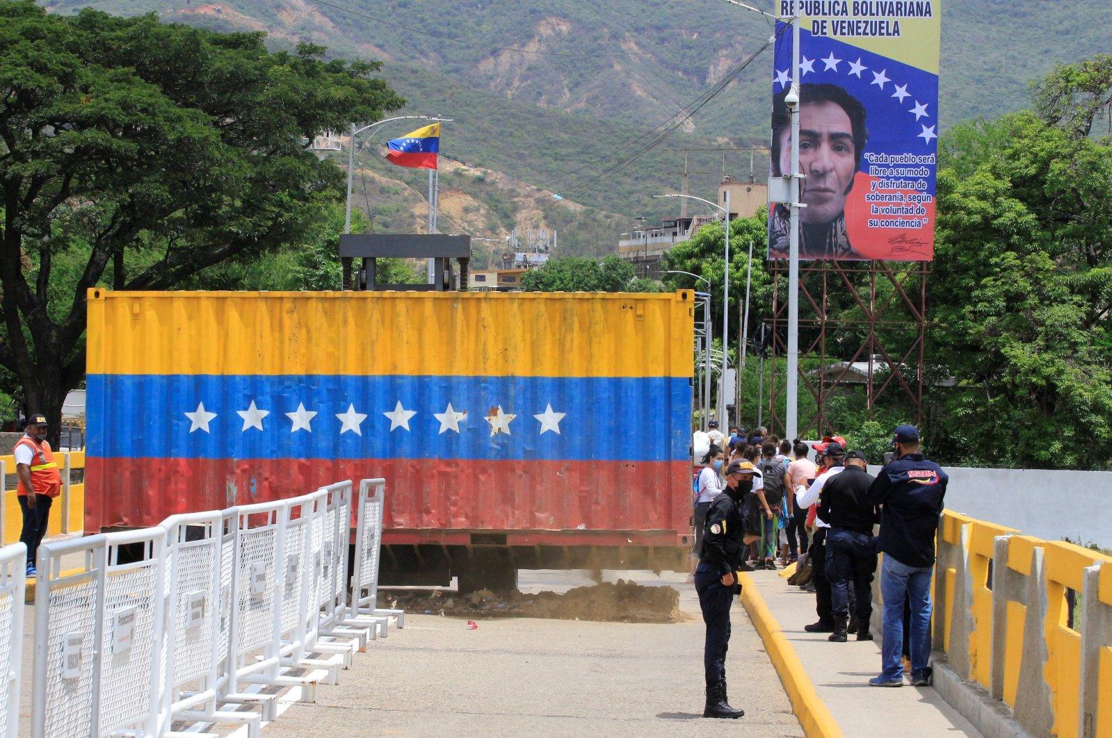 Authorities walk next to one of the containers that block the border crossing between Colombia and Venezuela, at the Simon Bolivar international bridge, in San Antonio del Tachira, Venezuela, Oct. 4, 2021. (EPA Photo)