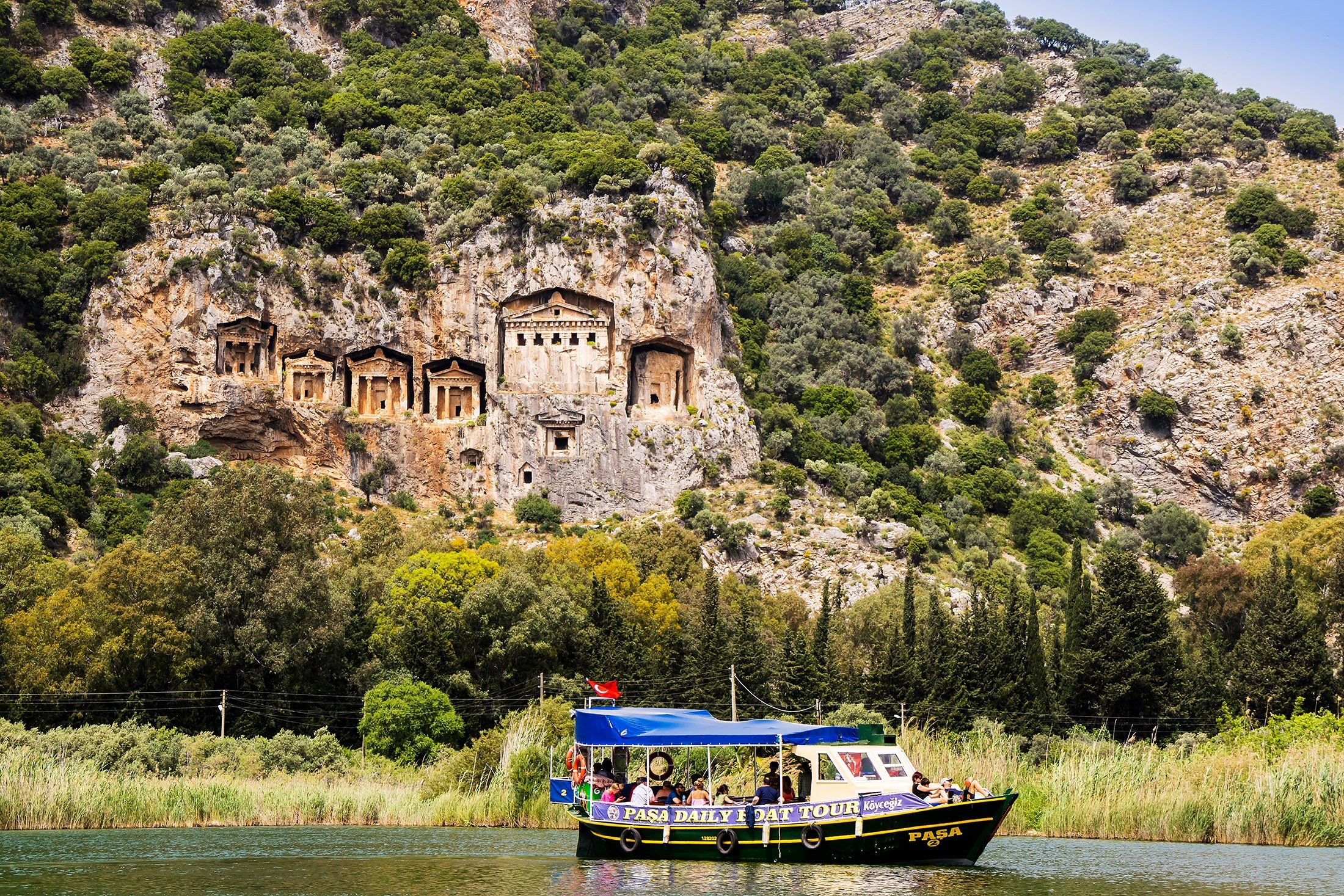 A small boat with tourists on the Dalyan River, Dalyan, Turkey. (Shutterstock Photo)