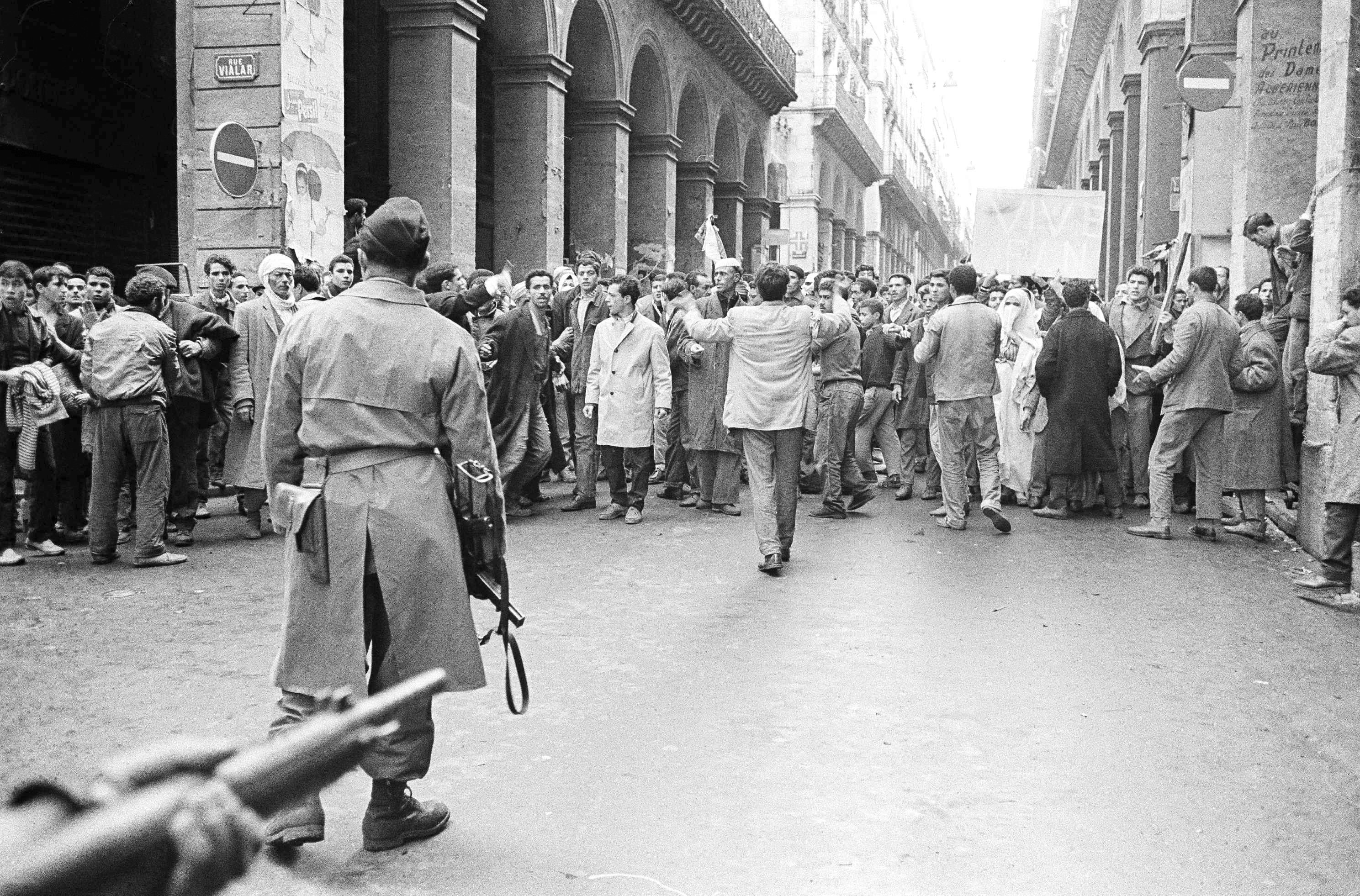 Armed French soldiers (foreground) face a shouting mob of Algerians at an entrance to the Casbah native quarter in Algiers, Dec. 14, 1960. (AP Photo)