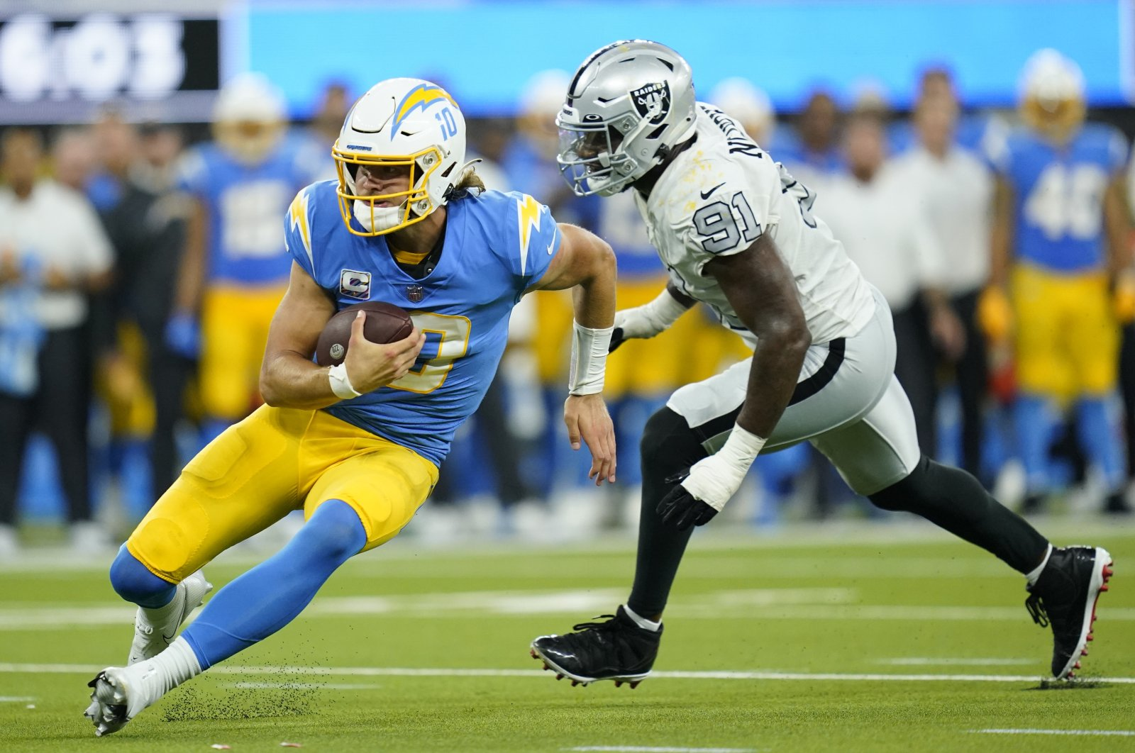 Los Angeles Chargers quarterback Justin Herbert runs with the ball as Las Vegas Raiders defensive end Yannick Ngakoue defends during the second half of an NFL football game, Inglewood, California, U.S., Oct. 4, 2021. (AP Photo)