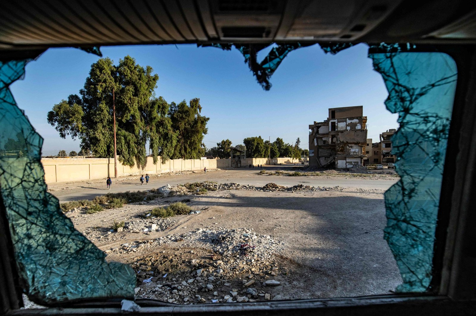 Syrian students walking to school are seen through shattered glass in the northern city of Raqqa, Syria, Sept. 23, 2021. (AFP Photo)