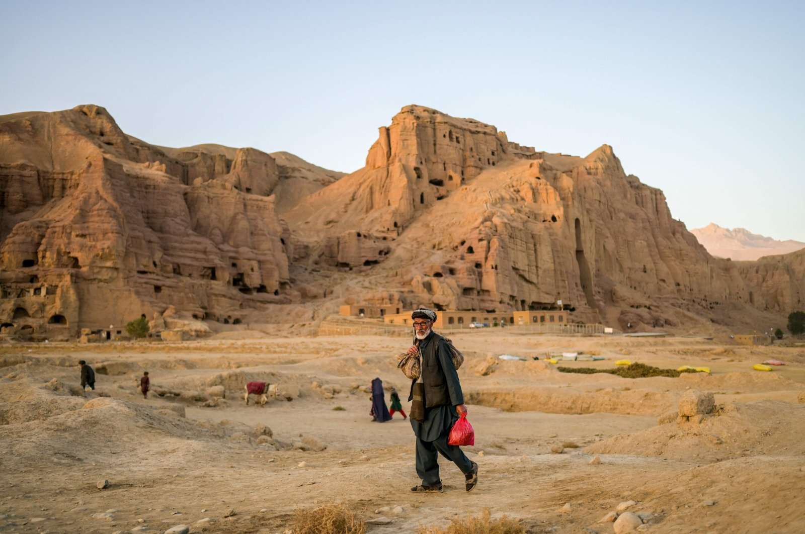A Hazara man walks home near the cliffs pockmarked by caves where people still live as they did centuries ago in Bamiyan, Afghanistan, Oct. 3, 2021. (AFP Photo)