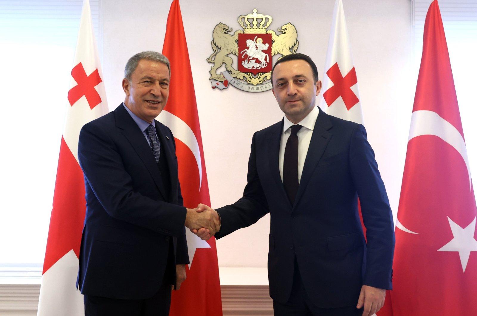 Defense Minister Hulusi Akar shakes hands with Georgian PM Garibashvili in Tibilisi, Monday, Oct. 4, 2021. (AA Photo)
