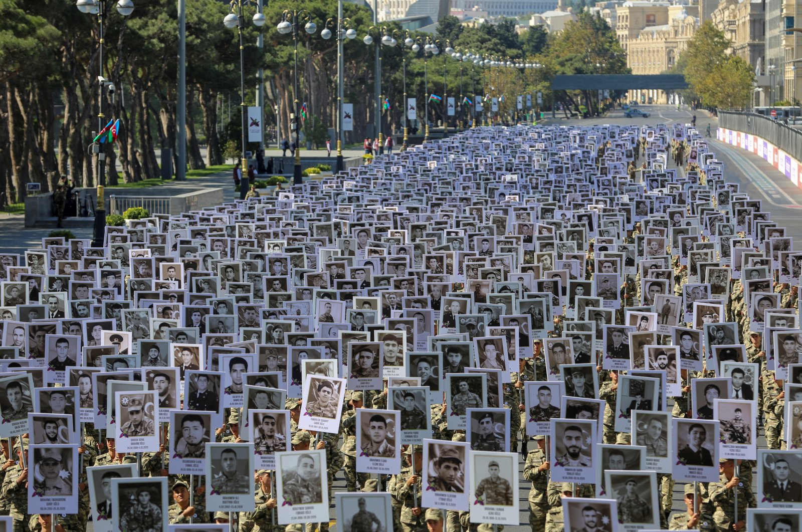 Soldiers carry portraits of Azerbaijani service members killed in the recent conflict over the region of Nagorno-Karabakh during a commemoration on its first anniversary, in Baku, Azerbaijan, Sept. 27, 2021. (Reuters Photo)
