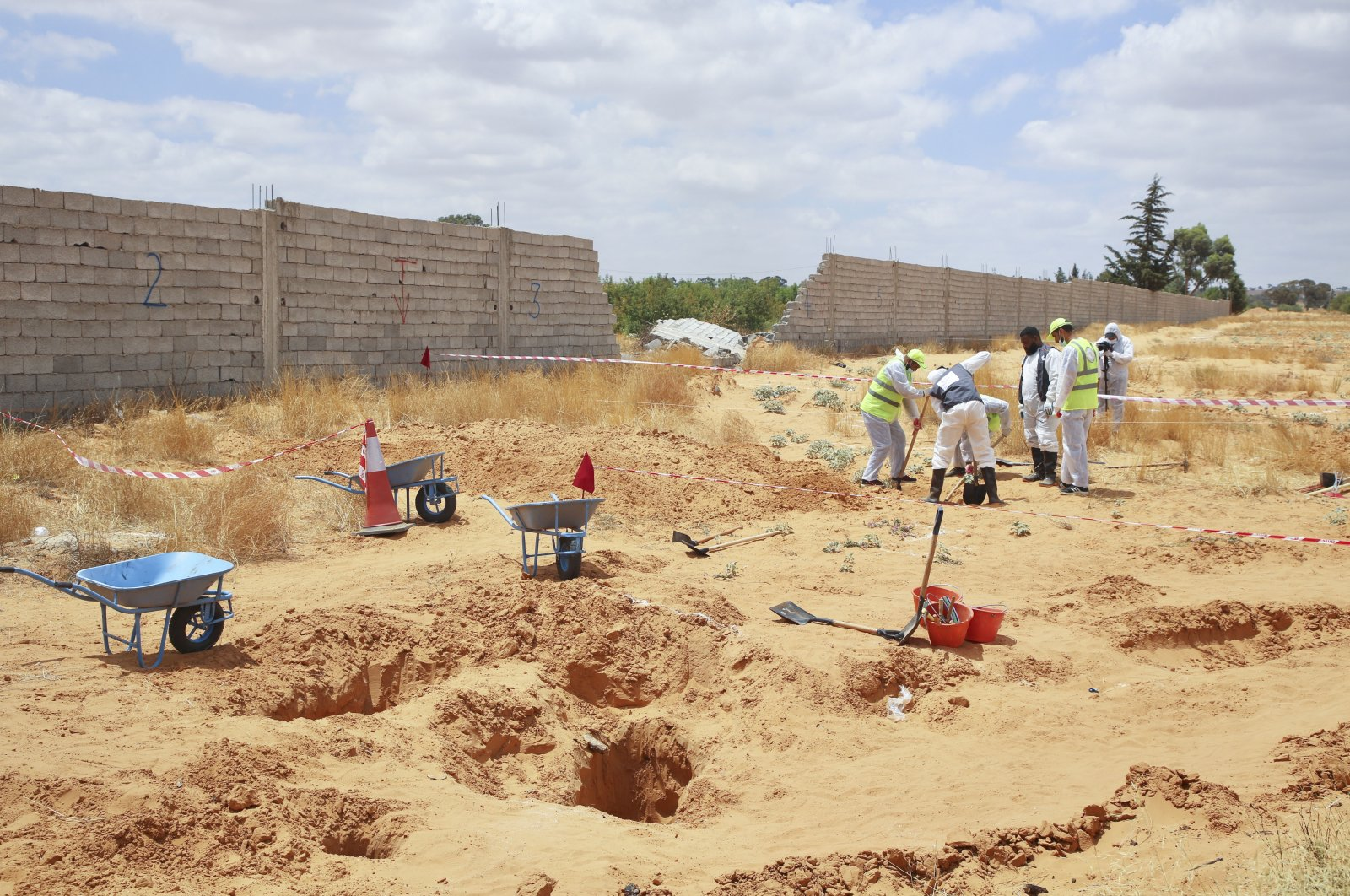 The Libyan Ministry of Justice employees dig at a site of a suspected mass grave in the town of Tarhuna, Libya, June 23, 2020. (AP File Photo)