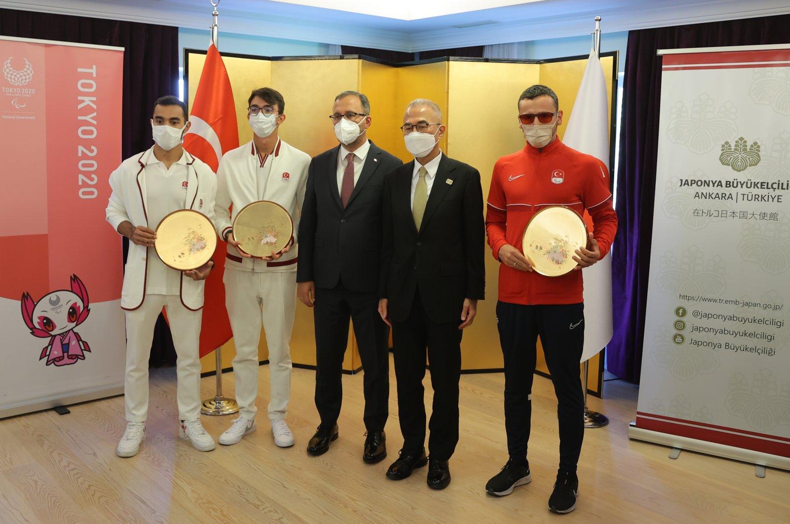Youth and Sports Minister Mehmet Muharrem Kasapoğlu (C), Japanese Ambassador Suzuki Kazuhiro, and Olympic athletes Mete Gazoz, Ferhat Arıcan and Oğzu Akbulut are seen at the Japanese Embassy in Ankara, Turkey, Oct. 4, 2021 (AA Photo)