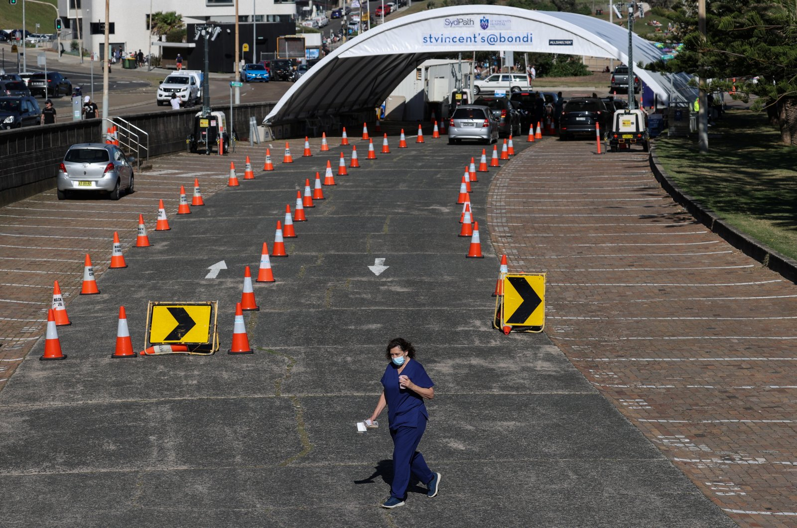 A health worker walks from the Bondi Beach drive-through COVID-19 testing center during an outbreak lockdown in Sydney, Australia, Oct. 5, 2021.  (Reuters Photo)