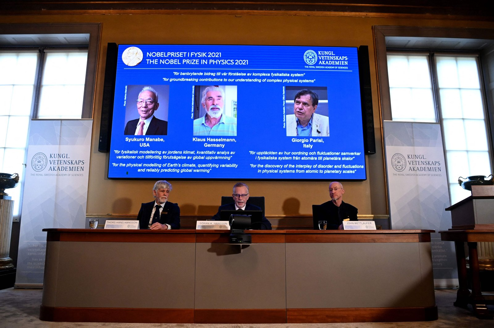 Goran K. Hansson (C), Secretary General of the Royal Swedish Academy of Sciences, and members of the Nobel Committee for Physics Thors Hans Hansson (L) and John Wettlaufer (R) sit in front of a screen displaying the co-winners of the 2021 Nobel Prize in Physics (L-R) Syukuro Manabe (U.S.-Japan), Klaus Hasselmann (Germany) and Giorgio Parisi (Italy) at the Royal Swedish Academy of Sciences in Stockholm, Sweden, Oct. 5, 2021. (AFP Photo)