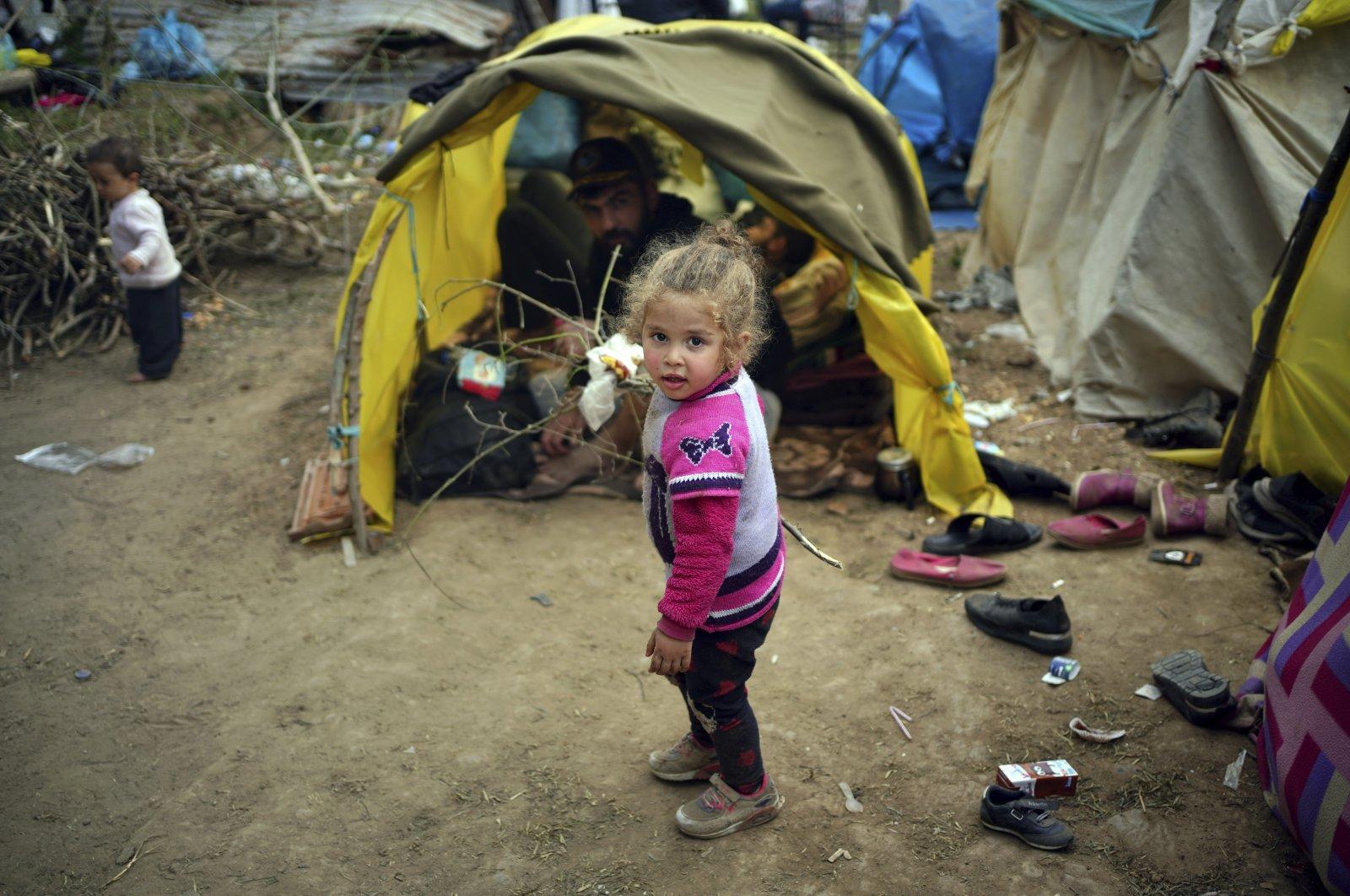 A child walks next to tends in a migrant camp set up near the Turkish-Greek border in Pazarkule, Edirne region, northwestern Turkey, March 10, 2020. (AP Photo)