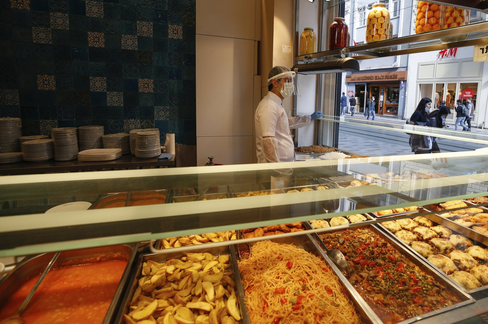 A restaurant worker waits for customers at a restaurant on Istiklal Avenue, the main shopping street in Istanbul, Turkey, June 1, 2020. (AP Photo)