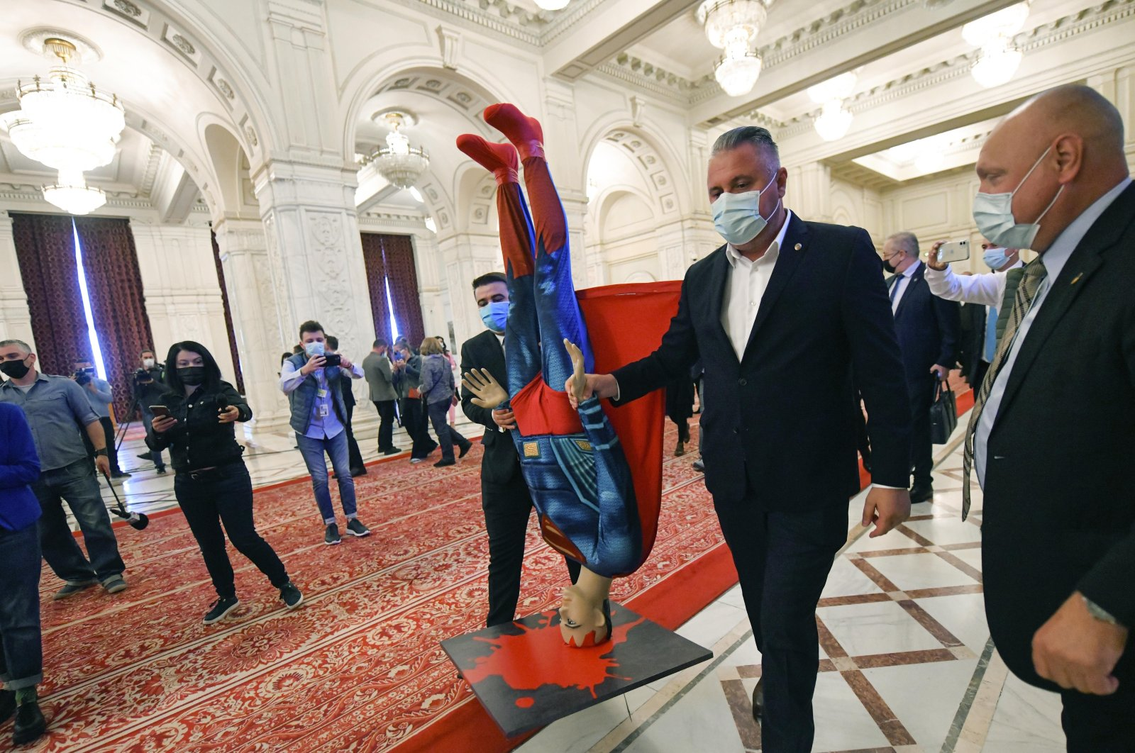 Men carry a mannequin depicting Superman ahead of a no confidence vote against Romanian Prime Minister Florin Citu's government in Romania's parliament in Bucharest, Romania, Oct. 5, 2021. (AP Photo)