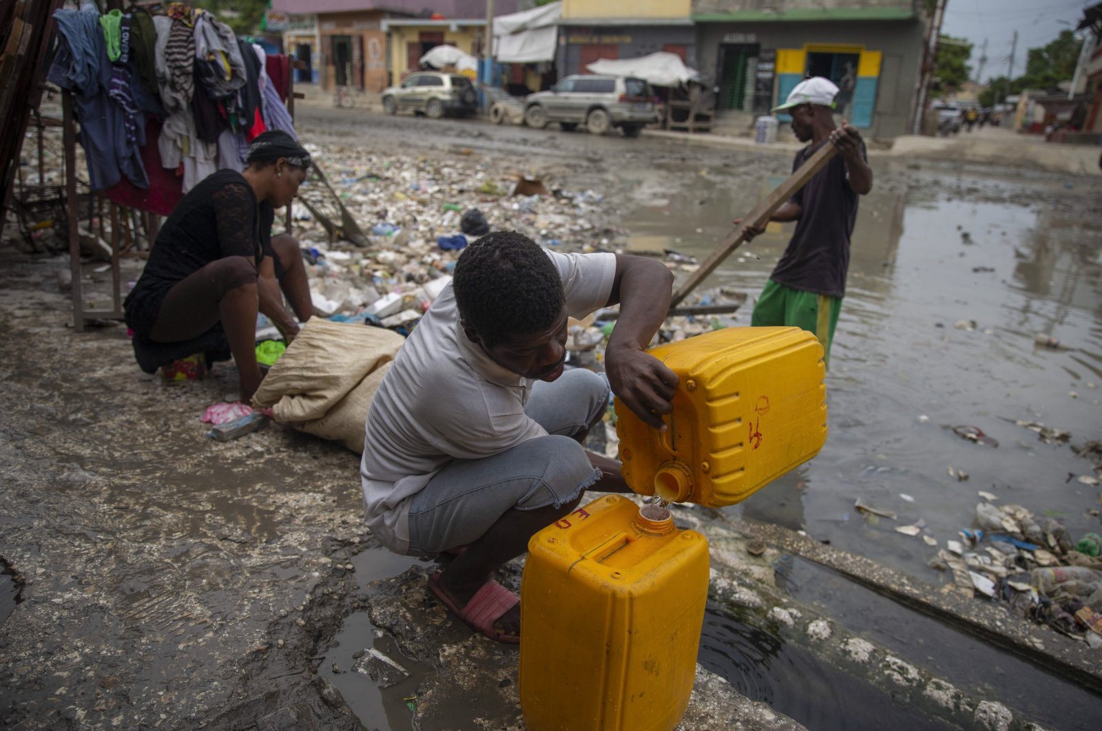A man collects water next in a flooded street, in the Portail neighborhood of Port-au-Prince, Haiti, Oct. 4, 2021. (AP Photo)